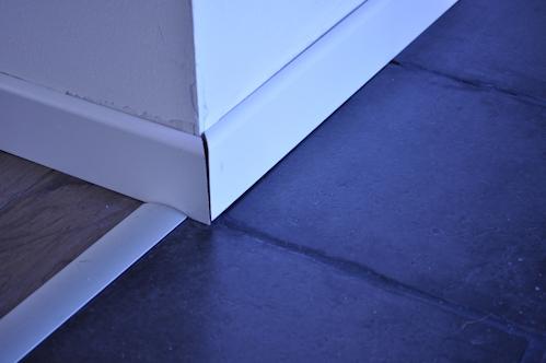 Plinthes blanches en bois posées sur du carrelage gris